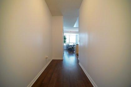Foyer With Laminate Flooring & Mirrored Closet.