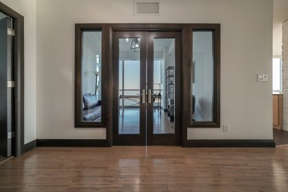 Hallway With Customized Mahogany Doors and Millwork Wood Framing Throughout.