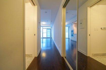 Foyer With Mirrored Closet & Hardwood Flooring Throughout.