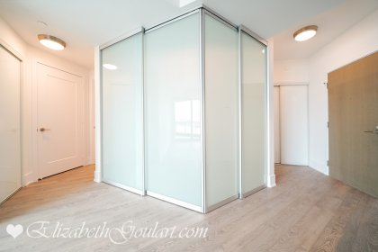 Master Bedroom With Glass Sliding Doors & Laminate Flooring.