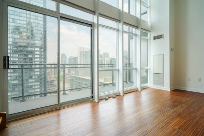 Bright Floor-To-Ceiling Windows With Laminate Flooring Facing Terrace CN Tower Views.
