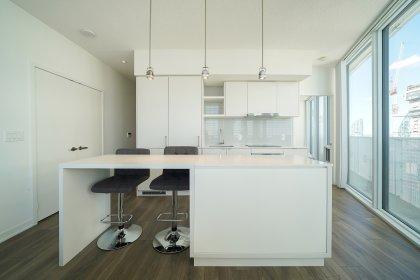 Open Concept Kitchen Area With Bright Wrap Around Windows & Laminate Flooring Facing Stunning Lake Views.