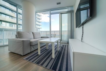 Open Concept Living And Dining Areas With Bright Wrap Around Windows & Laminate Flooring Facing Stunning Lake Views.