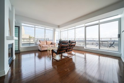 Bright Floor-To-Ceiling Wrap Around Windows With Automated Blinds, Gas Fireplace And Gleaming Hardwood Flooring With A Walk-Out To The Private Terrace