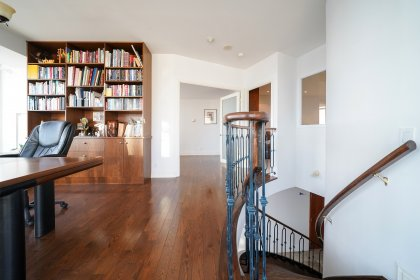An Open Concept Library or Home Office With Built-In Shelving, Gleaming Hardwood Flooring and Wrap Around Windows With Automated Shades Onlooking Spec