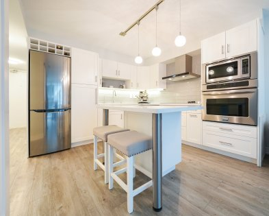 Designer Kitchen Cabinetry With New Stainless Steel Appliances, Stone Counter Tops, An Undermount Sink, Valance Lighting & A Breakfast Bar.