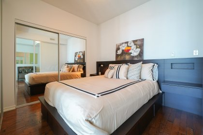 A Spacious Sized Master Bedroom With 2 Glass Sliding Doors & A Large Mirrored Closet.