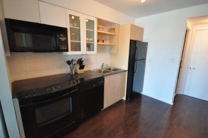 Kitchen with upgraded Hardwood flooring, granite counter top and ceramic backsplash.