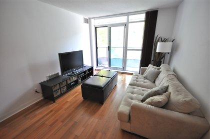 Bright Floor-To-Ceiling Windows With Laminate Flooring.