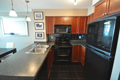 Designer Kitchen Cabinetry With Ceramic Backsplash & A Breakfast Bar.