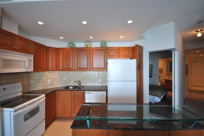 Designer Kitchen Cabinetry With Granite Counter Tops, Ceramic Backsplash, Pot Lighting, Undermounted Sink & A Glass Breakfast Bar.