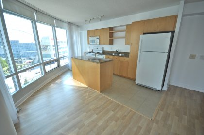 Bright Floor-To-Ceiling Windows With Laminate Flooring Throughout & A Separate Dining Area.