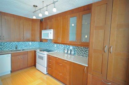 Designer Kitchen Cabinetry With Custom Italian Tile Backsplash, Stone Counter Tops With Breakfast Bar, Undermount Sink & Valance Lighting.