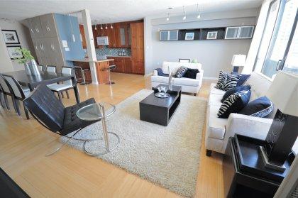 Spacious Living Area With Floor-To-Ceiling Windows, Hardwood Flooring Throughout Facing Stunning Lake Views.