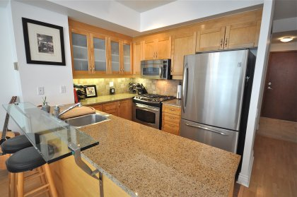 Designer Kitchen Cabinetry With Stainless Steel Appliances, Gas Stove, Granite Counter Tops, Ceramic Backsplash, Valance Lighting & A Glass Breakfast