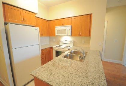 Designer Kitchen Cabinetry With Granite Counter Tops, Ceramic Backsplash & A Breakfast Bar.