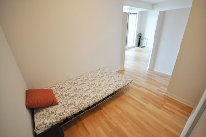 Spacious Sized Bedroom With Hardwood Flooring.