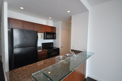 Designer Kitchen Cabinetry, Granite Counter Tops, Pot Lighting & A Glass Breakfast Bar.