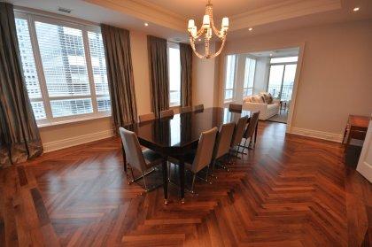 Elegant Dining Area With Coffered Ceiling, Pot Lighting & Hardwood Flooring.