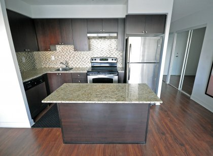 Designer Kitchen Cabinetry With Stainless Steel Appliances, Granite Counter Tops With Centre Island & Laminate Flooring Throughout.