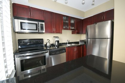Designer Kitchen Cabinetry With Stainless Steel Appliances, Granite Counter Tops, Breakfast Bar & A Window Onlooking The Front.