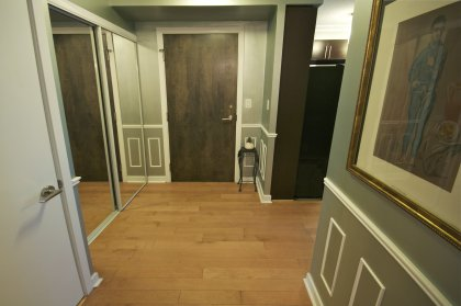 Suite Foyer With Mirrored Closets, Panel Mouldings, Designer Paint Colours & Hardwood Flooring.