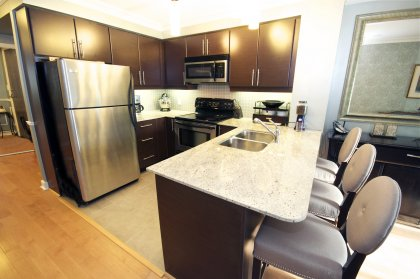 Designer Kitchen Cabinetry With Stainless Steel Appliances, Granite Counter Tops, An Undermount Sink & Valance Lighting.