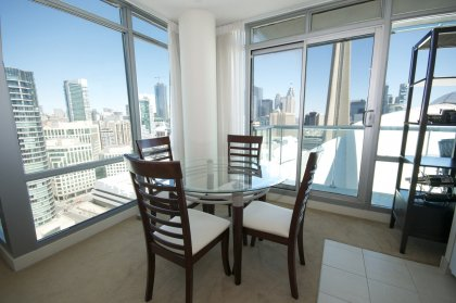Open Concept Dining Area With Bright Floor-To-Ceiling Wrap Around Windows Facing Unobstructed C.N. Tower Views.