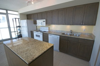 Designer Kitchen Cabinetry With Granite Counter Tops, Undermount Lighting & A Centre Island.