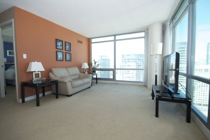 Open Concept Living Area With Bright Floor-To-Ceiling Wrap Around Windows Facing Unobstructed C.N. Tower Views.