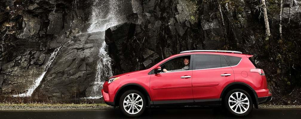 Red RAV4 In front of waterfall