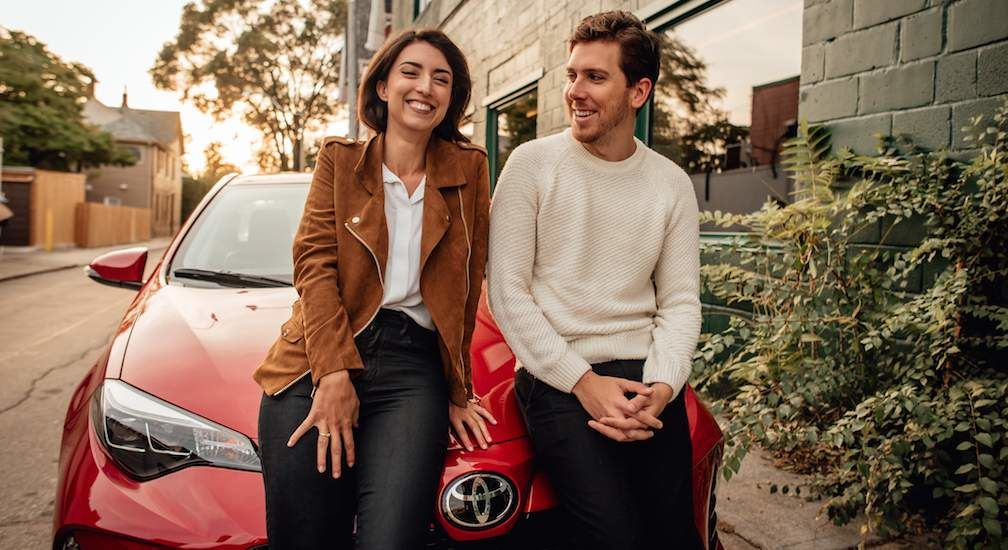 Couple Standing in Front of Toyota Corolla in Red