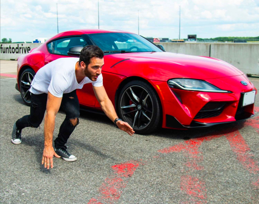 Man pretending to race a GR Supra in Renaissance Red