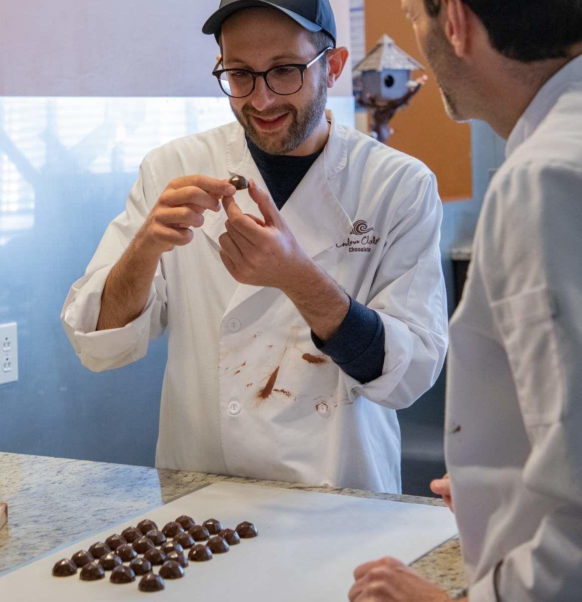 Michael avec Carl Pelletier, de la chocolaterie Couleur Chocolat, confectionnant du chocolat