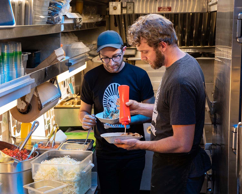 Michael et Kevin Mair préparent des tacos au camion de restauration Tacofino, à Tofino (C.-B.)