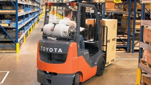 Toyota core internal combustion cushion tire forklift moving pallets around corner in warehouse