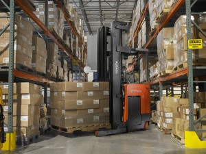 Electric Reach Truck loaded turning in warehouse aisle