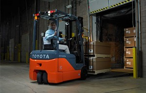 3-wheel electric forklift loading pallets into truck
