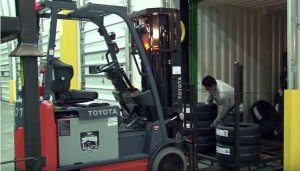 Forklift Unloading Tires into Truck