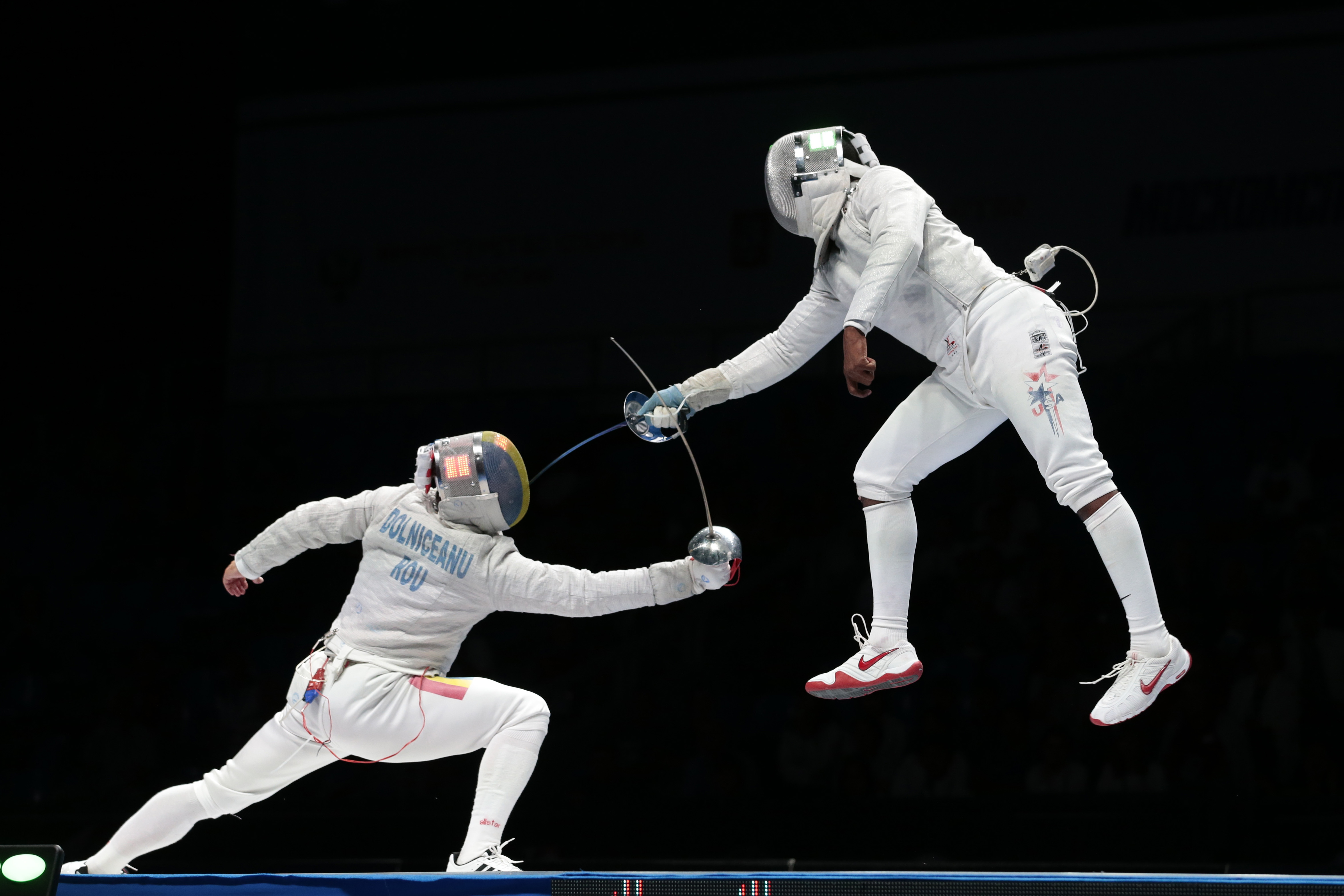 Tiberiu Dolniceanu, of Romania, left, and Daryl Homer, of the United States, right, in action during his semifinal match at sabre competition at the fencing World championships in Moscow, Russia, on Tuesday, July 14, 2015. (AP Photo/Ivan Sekretarev)