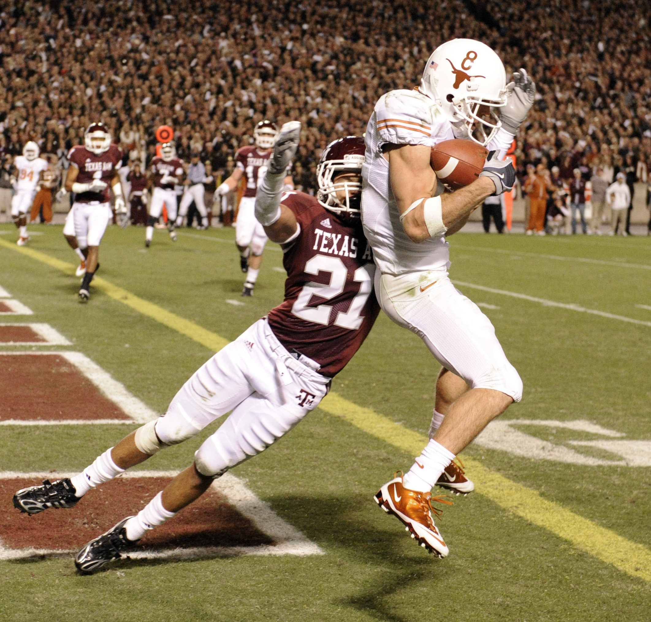 Texas wide receiver Jordan Shipley (8) catches a pass for a touchdown as Texas A&M cornerback Justin McQueen (21) defends during the first quarter of an NCAA college football game Thursday, Nov. 26, 2009, in College Station, Texas. (AP Photo/Dave Einsel)