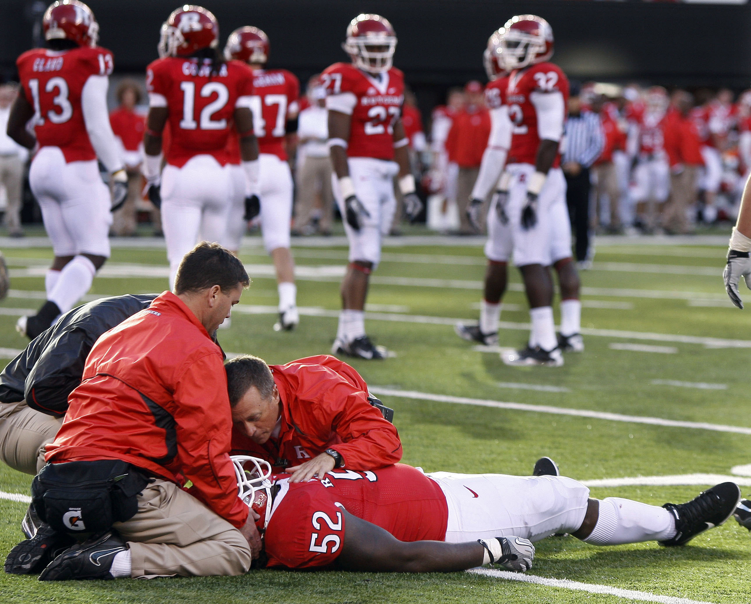 FILE - In this  Oct. 16, 2010,  file photo, Rutgers defensive tackle Eric LeGrand (52) is treated on the field after colliding with Army's Malcolm Brown while trying to make the tackle during the second half of an NCAA football game in East Rutherford, N.J. This Sunday will mark one year since LeGrand was paralyzed while making a tackle on a kick return against Army. The 21-year-old is wheelchair-bound, unable to move below his shoulders, but he still leads a full life and believes he will walk again.  (AP Photo/Mel Evans, File)