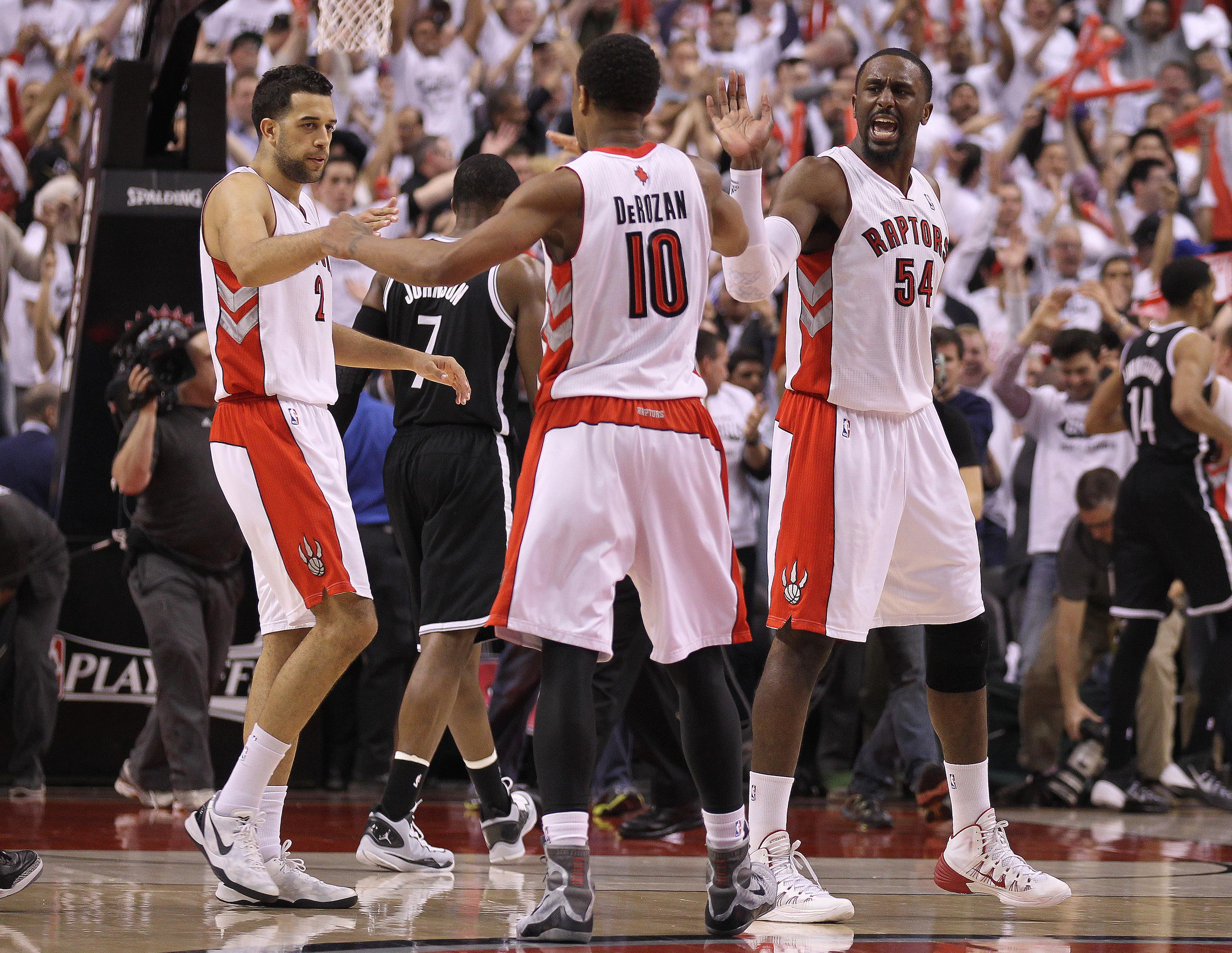 TORONTO, ON - APRIL 22: DeMar DeRozan #10 of the Toronto Raptors celebrates a win with teammates Patrick Patterson #54 and Landry Fields #2 against the Brooklyn Nets in Game Two of the NBA Eastern Conference Quarterfinals at the Air Canada Centre on April 22, 2014 in Toronto, Ontario, Canada. The Raptors defeated the Nets 100-95 to even the series 1-1. NOTE TO USER: user expressly acknowledges and agrees that, by downloading and/or using this Photograph, user is consenting to the terms and conditions of the Getty Images License Agreement. (Photo by Claus Andersen/Getty Images)