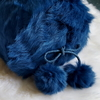 Electric blue kid skin bolster cushion with pom poms. 600x600px
