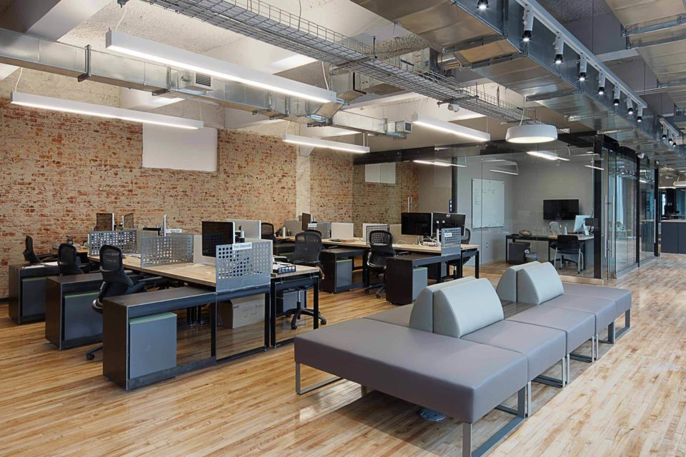 Members of Trifecta Technologies' team sit in sections that include couches for extra space and a change of view.