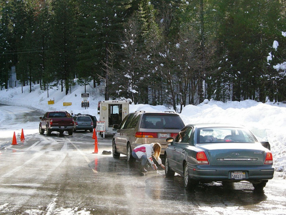 Trip photo #21/77 A Tire Chain salesvan and lady putting on chains near Yosemite Park Entrance