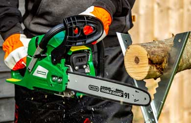 Gloved hand using a chainsaw to cut a log