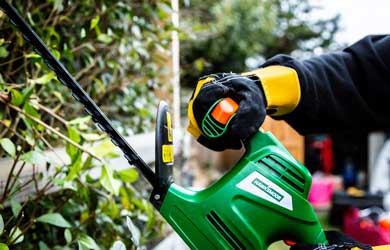 Gloved hand using a hedge trimmer