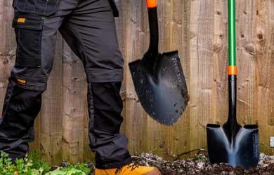 Man's leg next to two shovels