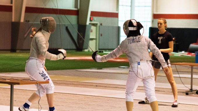Sophomore sabre Kerry Plunkett (background) watches while sophomore sabre Malia Hee (right) and freshman sabre Eva Hinds fence during practice on Friday in the Student Pavilion.   JAMIE COTTRELL / THE TEMPLE NEWS